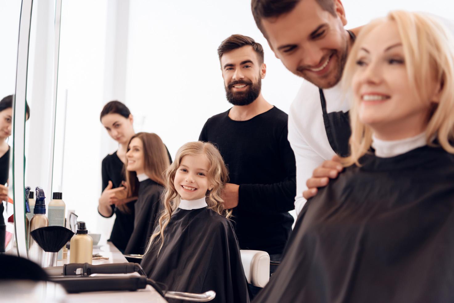 Tim frizera sa sretnima klijentima u frizerskim stolicama